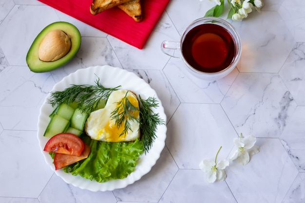 Fried eggs with lettuce, cucumber and tomato slices on a light background