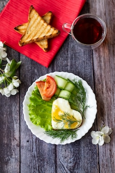 Fried eggs with lettuce, cucumber and tomato slices on wooden background