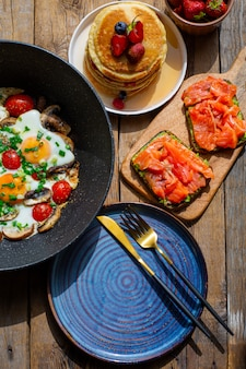 Fried eggs with mushrooms and green onions.bright eggs with tomatoes, mushrooms and onions