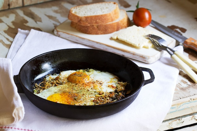 Fried eggs with onions and spices in a cast iron skillet.