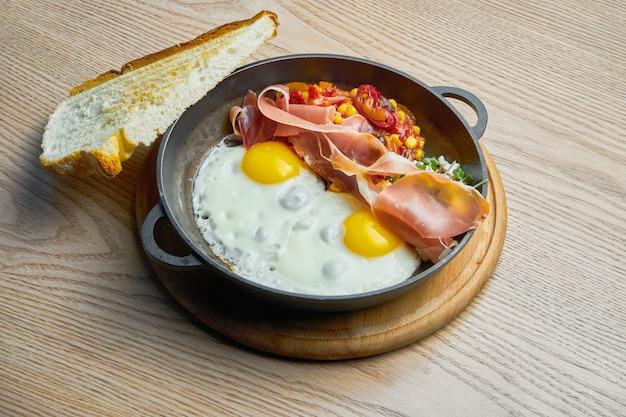 Яичница с прошутто, фасолью и перцем чили и кукурузой в томатном соусе подается в мини-сковороде. вкусная еда на завтрак
