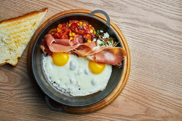 Яичница с прошутто, фасолью и перцем чили и кукурузой в томатном соусе подается в мини-сковороде.