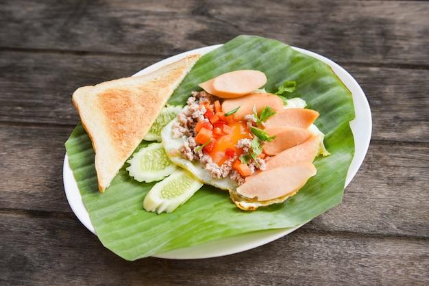 Яичница с колбасой, свининой, огурцом и хлебом на завтрак на фоне банановых листьев