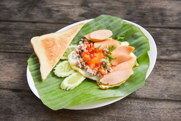 Fried eggs with sausage cucumber pork and bread for breakfast on banana leaf background