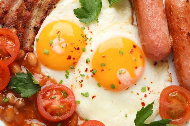 Fried eggs with sausages, vegetables and spices on whole background, close up