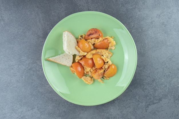 녹색 접시에 얇게 썬 토마토와 함께 튀긴 계란입니다.