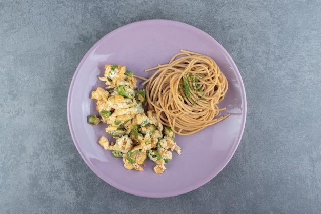 보라색 접시에 스파게티와 튀긴 계란입니다.