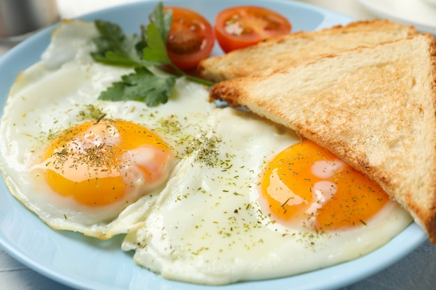 Fried eggs with spices on whole background, close up