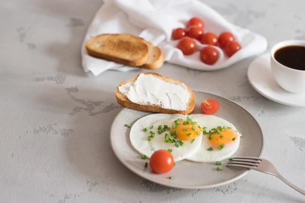 グレーのプレートにトマトとネギ、トースト、明るい背景にブラックコーヒーと目玉焼き
