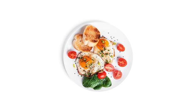 야채와 흰색 배경에 고립 된 하얀 접시에 토스트와 튀긴 계란. 아름다운 아침. 고품질 사진