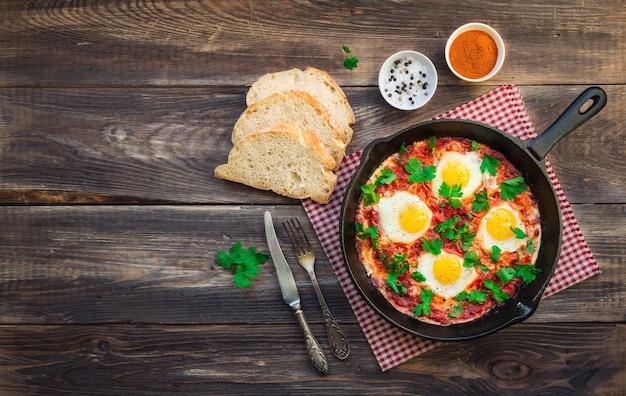 素朴な木製の背景に鉄のフライパンで野菜とトマトソースと目玉焼き