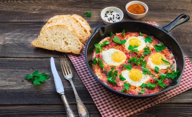 Жареные яйца с овощами и томатным соусом в железной сковороде на деревенском деревянном фоне
