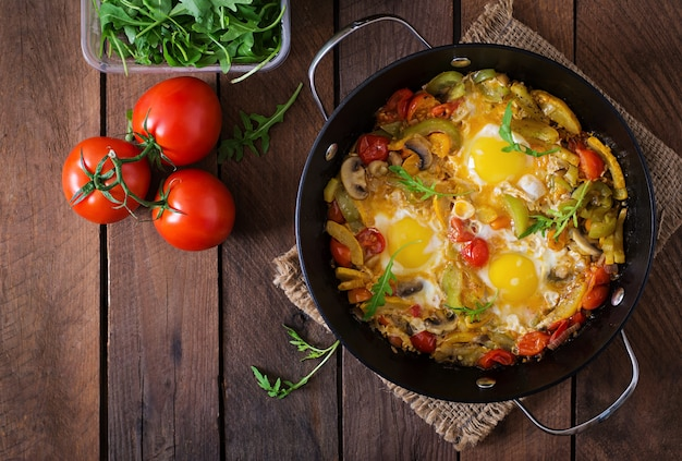 Fried eggs with vegetables in a frying pan on a wooden table