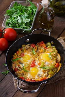 Fried eggs with vegetables in a frying pan