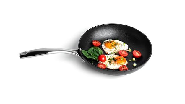 흰색 배경에 고립 된 팬에 야채와 함께 튀긴 계란. 아름다운 아침. 고품질 사진
