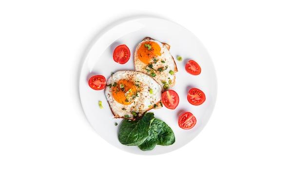 흰색 배경에 고립 된 흰색 접시에 야채와 함께 튀긴 계란. 아름다운 아침. 고품질 사진