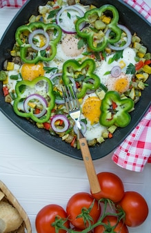 Fried eggs with vegetables in a pan. arabic cuisine proper nutrition.