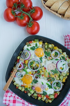 Fried eggs with vegetables in a pan. shakshuk. arabic cuisine proper nutrition. view from above.
