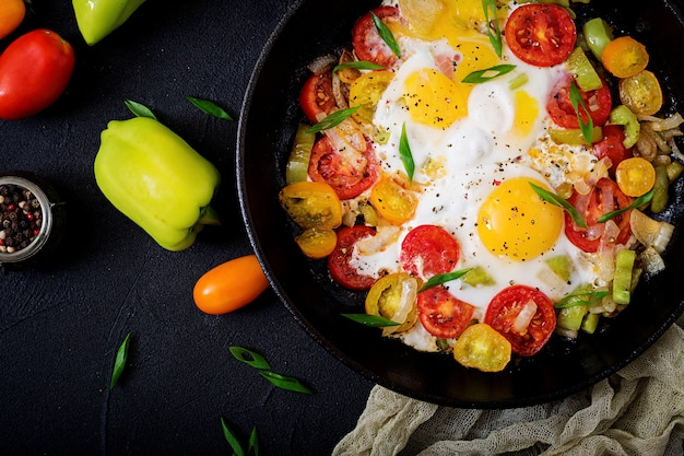 Fried eggs with vegetables - shakshuka in a frying pan on a black background. flat lay. top view