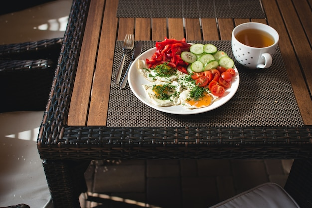 Fried eggs with vegetables and tea