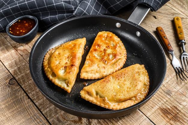 Жареные пикантные булочки с эмпанадами с начинкой из говядины на сковороде