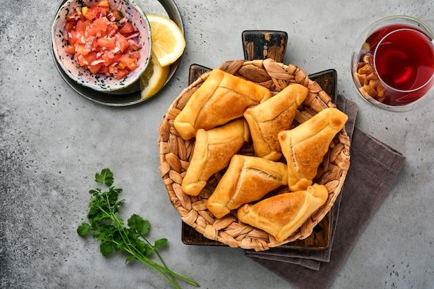 고수, 고기, 계란, 토마토 및 회색 배경에 칠리 소스와 함께 튀긴 엠파 나다. 칠레의 전형적인 요리. 라틴 아메리카 및 칠레 독립 기념일 개념.