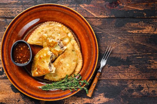 Жареные эмпанада с фаршем из говядины на тарелке с соусом чили