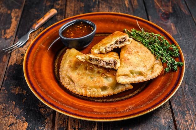 다진 쇠고기 고기와 함께 튀긴 엠파 나다를 칠리 소스와 함께 접시에 담았습니다.