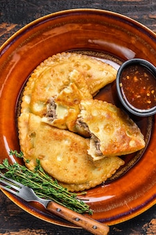 Fried empanadas with minced beef meat served on a plate with chili sauce