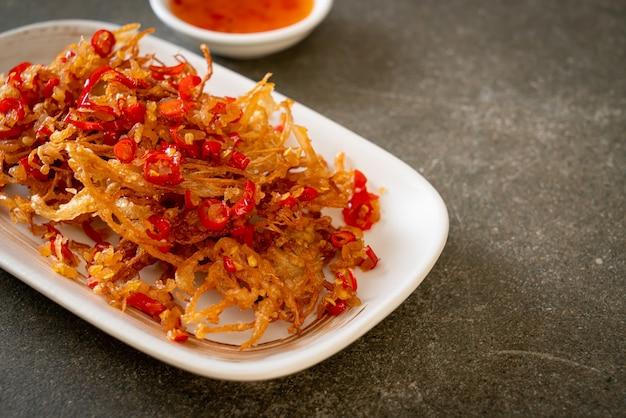 えのき茸の揚げ物または塩と唐辛子を添えたゴールデンニードルマッシュルーム-ビーガンとベジタリアンのフードスタイル