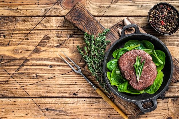 フィレミニョンのテンダーロインミートビーフステーキのフライパンにサラダを添えて揚げたもの。木製の背景。上面図。スペースをコピーします。