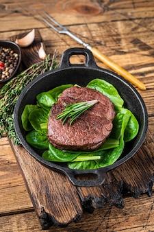 フィレミニョンのテンダーロインミートビーフステーキのフライパンにサラダを添えて揚げたもの。木製の背景。上面図。