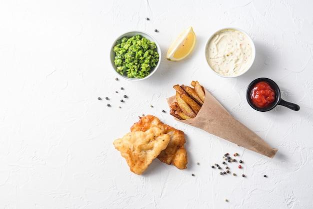 すべてのコンポーネントの古典的なレシピと白い背景の上の紙の円錐形の揚げフィッシュアンドチップス