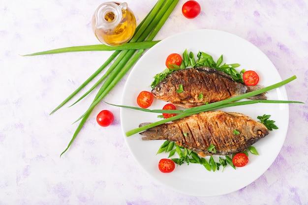 Карп из жареной рыбы и салат из свежих овощей. квартира лежала. вид сверху
