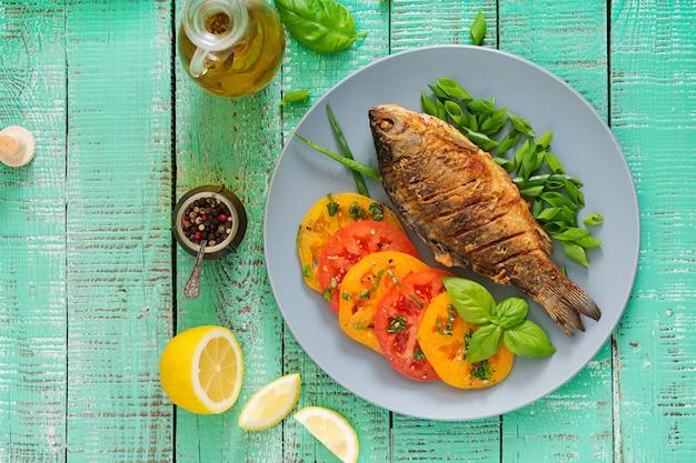 揚げ魚の鯉と木製のテーブルに新鮮な野菜のサラダ。フラット横たわっていた。上面図