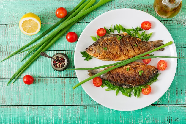 Fried fish carp and fresh vegetable salad on wooden table. flat lay. top view