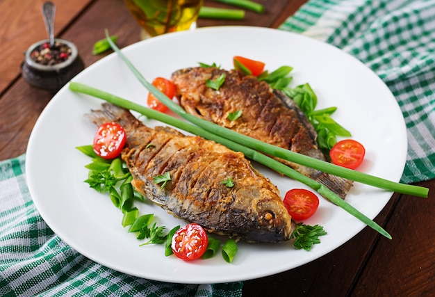 Fried fish carp and fresh vegetable salad on wooden table.