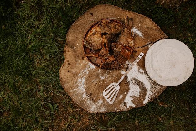 튀긴 생선 붕어는 흰 밀가루가 깔린 오래된 금이 간 나무 그루터기에 있는 접시에 놓여 있습니다
