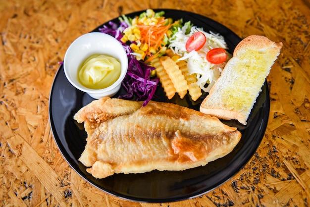 Жареное рыбное филе - стейк из рыбы с соусом, картофелем фри, хлебом и свежими овощами на тарелке