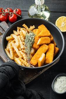 튀긴 생선 손가락 스틱 또는 검은 나무 테이블에 프라이팬 철 팬에 소스 세트와 함께 감자 튀김 생선