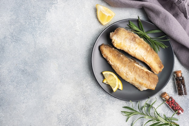 Жареный рыбный хек минтай и дольки свежего лимона.