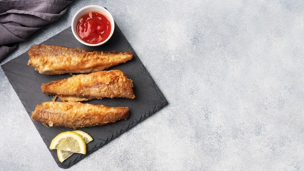 Fried fish hake pollock with tomato sauce and slices of fresh lemon. concept eating fatty fast food. grey concrete background copy space.
