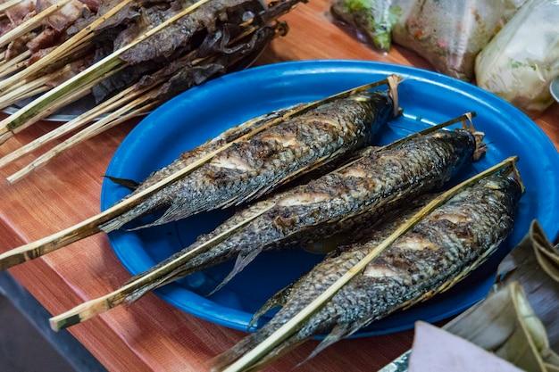 시장 상인의 카운터에서 그릴에 소금에 튀긴 생선. 전통적인 아시아 거리 음식입니다. 구운 생선 꼬치 - 라오스 스타일.