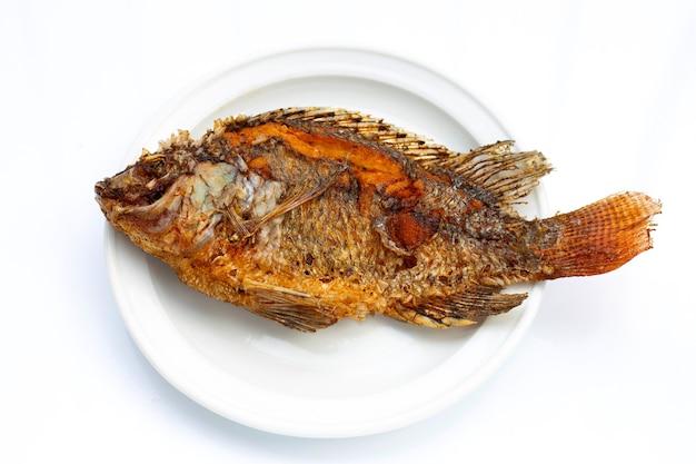 白い背景の上の白いプレートで揚げ魚。
