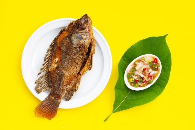 黄色の背景に白いプレートで揚げ魚。