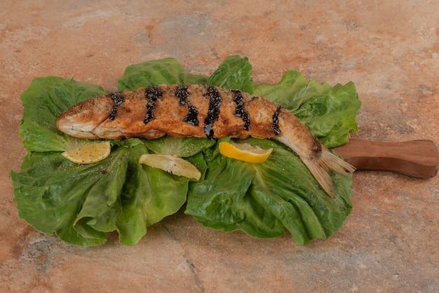 Pesce fritto su lattuga con fette di limone sul tavolo di marmo.