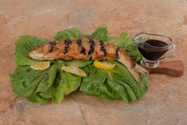 Fried fish on lettuce with lemon slices, pickles and pomegranate sauce.