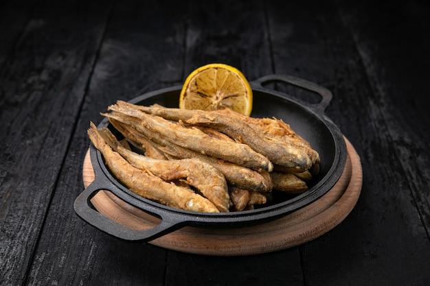 暗い木製のテーブルの上の黒い鋳鉄フライパンで揚げ魚