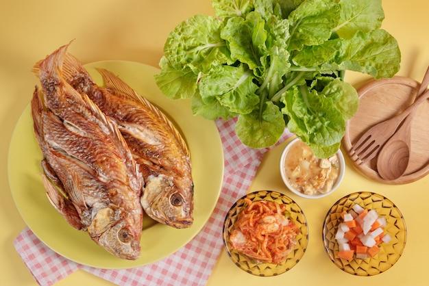 Жареная рыба на блюде с маринованными овощами и свежими зелеными листьями