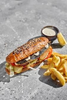 돌에 타르타르 소스와 감자 튀김을 곁들인 튀긴 생선 샌드위치
